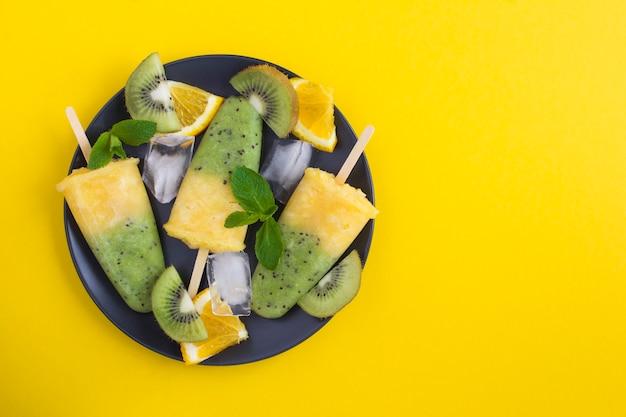 Vista superior de picolés com kiwi e frutas laranja na placa preta. copie o espaço.