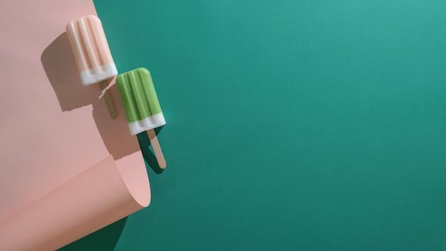 Vista superior de picolés de sabor de chá verde e morango e espaço da cópia no plano deite o fundo verde e rosa