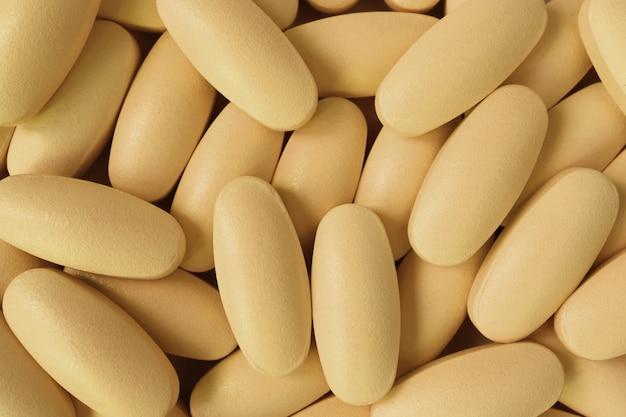 Vista superior, de, pilha, de, cremoso, oval amarelo, dado forma, pílulas, para, fundo