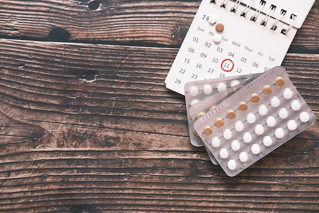 Vista superior de pílulas anticoncepcionais e um calendário na mesa de madeira