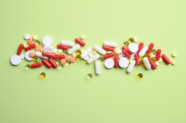 Vista superior de pílulas brilhantes coloridas na superfície verde pastel