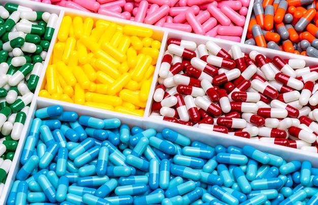 Vista superior de pílulas cápsulas coloridas em bandeja de plástico. indústria farmacêutica. cuidados de saúde e medicina.