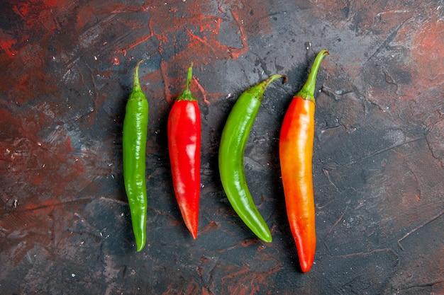 Vista superior de pimenta caiena em diferentes cores e tamanhos em um fundo de cor mista