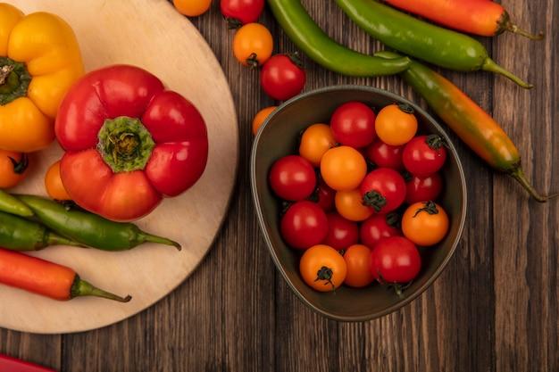 Vista superior de pimentas coloridas em uma placa de cozinha de madeira com tomate cereja em uma tigela na parede de madeira