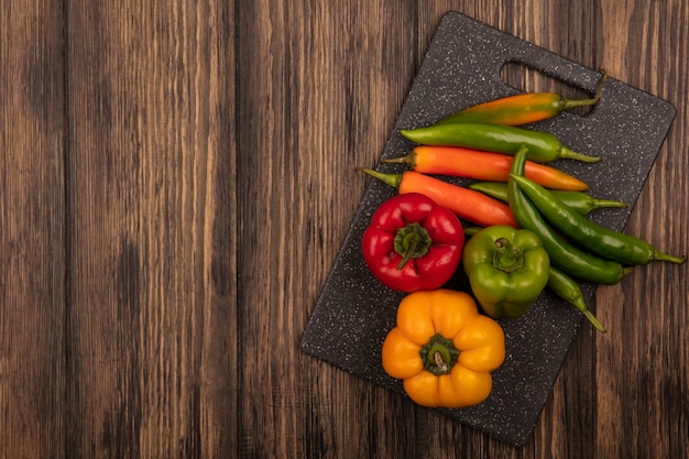 Vista superior de pimentas coloridas em uma placa de cozinha preta em um fundo de madeira com espaço de cópia