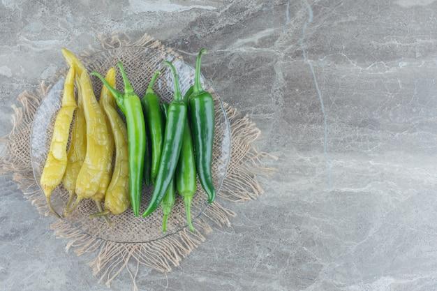 Vista superior de pimentas verdes em conserva e frescas na placa de vidro.