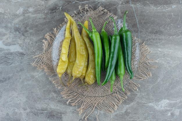 Vista superior de pimentas verdes frescas e enlatadas.