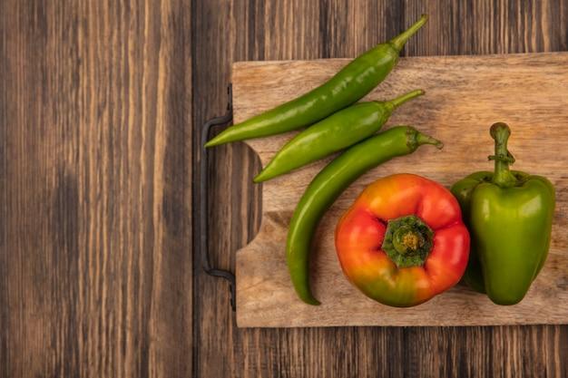 Vista superior de pimentas vermelhas e verdes saudáveis em uma placa de cozinha de madeira em uma superfície de madeira com espaço de cópia