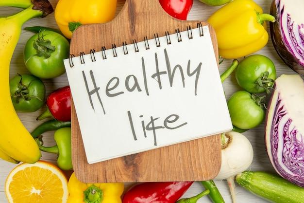 Vista superior de pimentões frescos com bananas verdes e repolho roxo no fundo branco dieta cor madura foto de salada de vida saudável