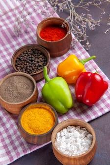 Vista superior de pimentões frescos com diferentes temperos em uma refeição de superfície cinza ingrediente alimentar veegtable