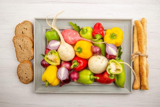 Vista superior de pimentões frescos com pão de rabanete e cebola na mesa branca