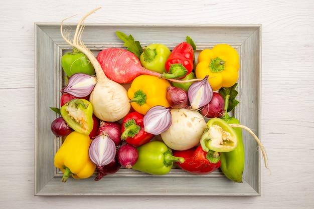 Vista superior de pimentões frescos com rabanete e cebola na mesa branca