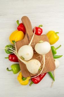 Vista superior de pimentões frescos com rabanete em um fundo branco cor de salada dieta saudável foto madura