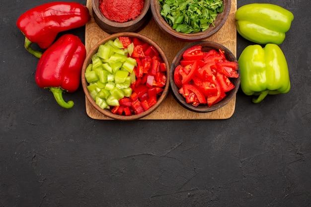 Vista superior de pimentões frescos com verduras em fundo cinza comida picante salada de comida