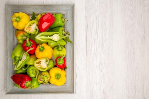 Vista superior de pimentões frescos dentro da moldura na mesa branca