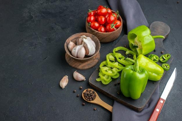 Vista superior de pimentões verdes cortados inteiros em uma faca de tábua de madeira preta na toalha de tomate e alho em tigelas na superfície preta afligida