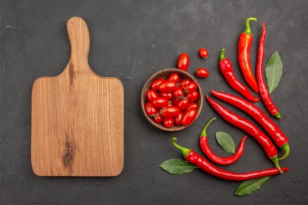 Vista superior de pimentões vermelhos e folhas de pagamento e uma tigela de tomates cereja e uma tábua de cortar na mesa preta com espaço de cópia