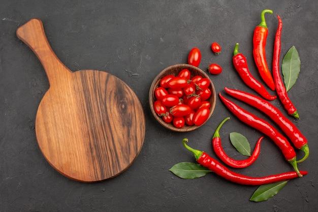 Vista superior de pimentões vermelhos e folhas pagas e uma tigela de tomates cereja e uma tábua oval de corte na mesa preta com espaço livre