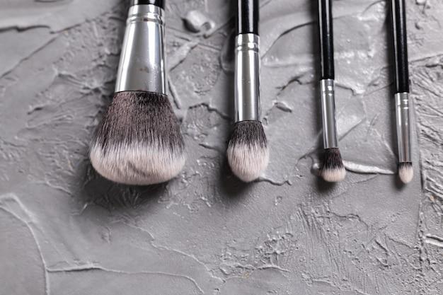 Vista superior de pincéis de maquiagem em fundo cinza com copyspace