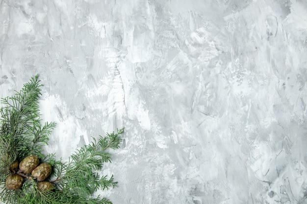 Vista superior de pinecones de galhos de pinheiro na superfície cinza