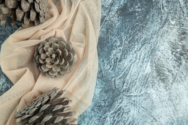 Vista superior de pinhas em xale bege em espaço livre de superfície escura