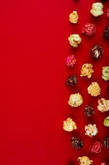 Vista superior de pipoca de chocolate e skittles no lado direito e vermelho com espaço de cópia