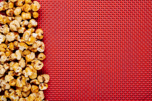 Vista superior de pipocas caramelizadas doces no lado esquerdo sobre fundo vermelho, com espaço de cópia