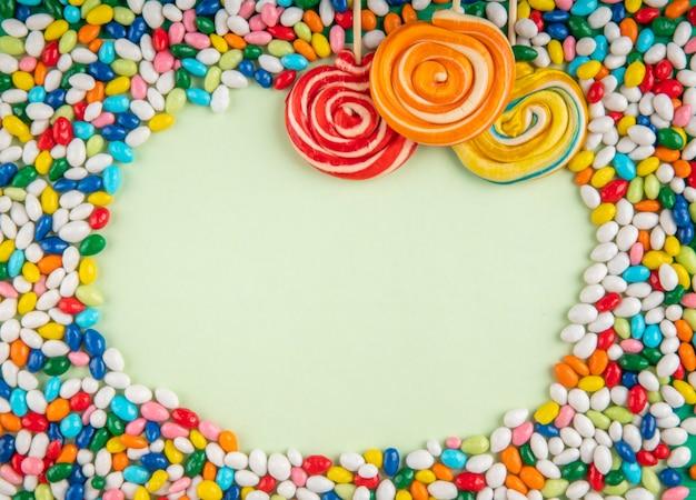 Vista superior de pirulitos coloridos e doces em esmalte multi-coloridas espalhadas sobre fundo branco, com espaço de cópia