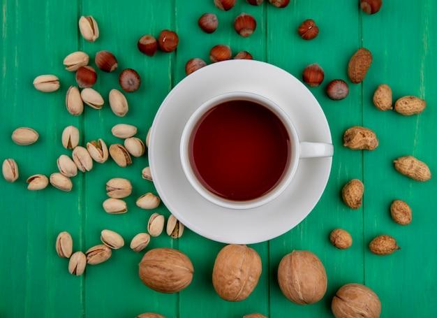 Vista superior de pistache com avelã, nozes e amendoim em tigelas de diferentes formatos e uma xícara de chá em uma superfície verde