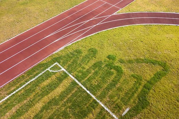 Vista superior de pistas de corrida vermelhas e gramado da grama verde. infraestrutura para atividades esportivas.