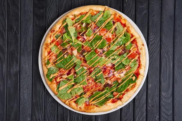 Vista superior de pizza com carne, pepino em conserva, cebola, salada de alface, tomate e molho barbecue