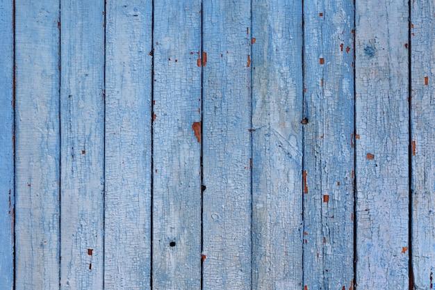 Vista superior de placas de madeira resistidas com tinta azul rachada.