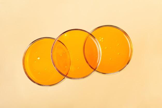 Vista superior de placas de petri com óleo cosmético dentro. fundo amarelo com espaço de cópia.