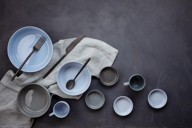 Vista superior de placas na moda modernas em bleu e em cores cinzentas. apartamento minimalista deitado com talheres