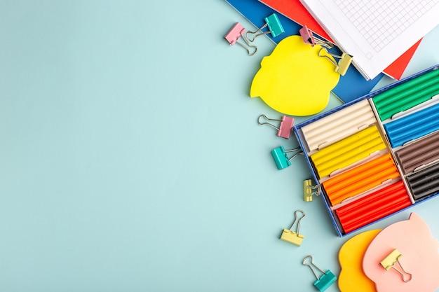Vista superior de plasticinas coloridas com cadernos em livro infantil de cor azul da parede