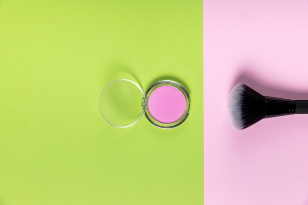 Vista superior de pó e pincel sobre fundo verde e rosa