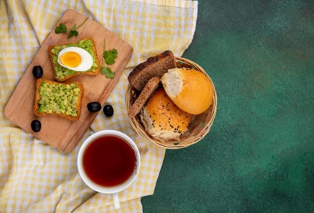 Vista superior de polpas de abacate em pães torrados com ovo na mesa de madeira da cozinha com um balde de pães na toalha de mesa xadrez amarela e cinza