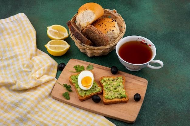 Vista superior de polpas de abacate em pães torrados com ovo na mesa de madeira da cozinha com uma xícara de chá e um balde de pães em gre