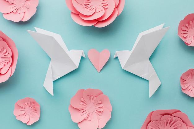 Vista superior de pombas de papel com coração e flores