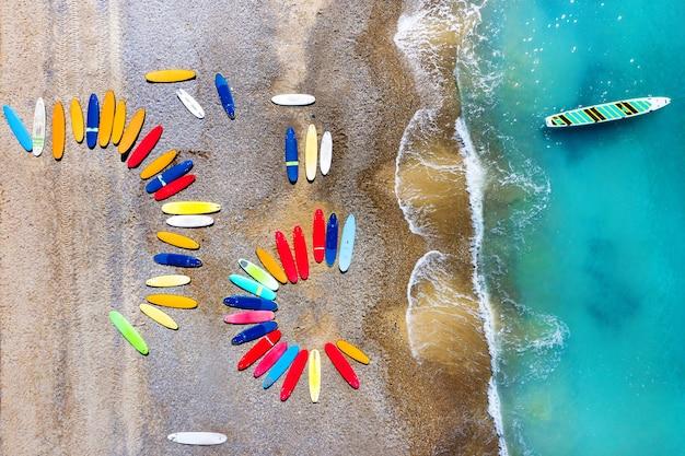 Vista superior de pranchas de surf coloridas caoticamente em uma praia de seixos na frança.