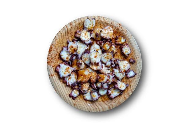Vista superior de prato de madeira com polvo galego (pulpo a la gallega em espanhol) - tipico de galicia, espanha