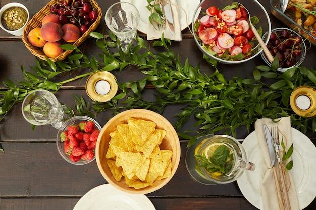 Vista superior de pratos coloridos de verão em uma mesa de jantar de madeira decorada com folhas frescas e elementos florais durante a festa ao ar livre