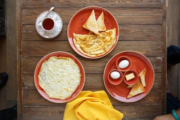 Vista superior de pratos de omelete e ovos cozidos, torradas e manteiga