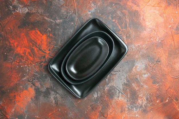 Vista superior de pratos pretos ovais e retangulares em superfície vermelho escuro