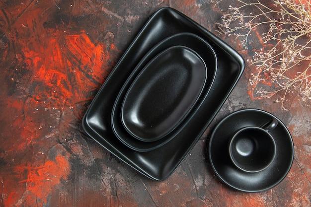 Vista superior de pratos pretos ovais e retangulares, xícara e pires pretos na superfície vermelha escura