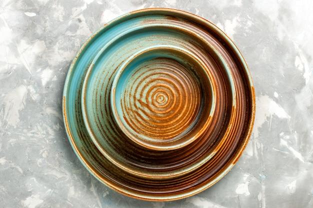 Vista superior de pratos redondos marrons vazios de diferentes tamanhos isolados na superfície cinza claro
