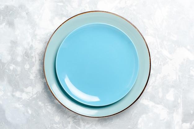 Vista superior de pratos redondos vazios azuis na superfície branca