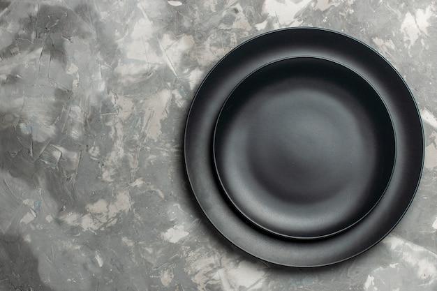 Vista superior de pratos redondos vazios de cor preta em superfície cinza