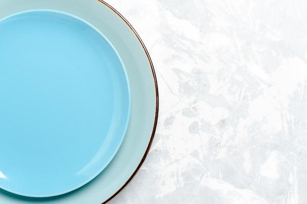 Vista superior de pratos redondos vazios ed azul na mesa branca
