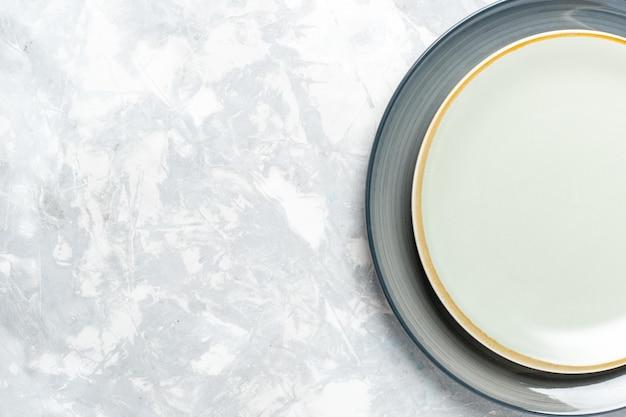 Vista superior de pratos redondos vazios na mesa branca